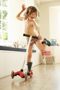 Tactile Sensory Issues for an Over Responsive System shown by a boy riding a scooter in his underwear.
