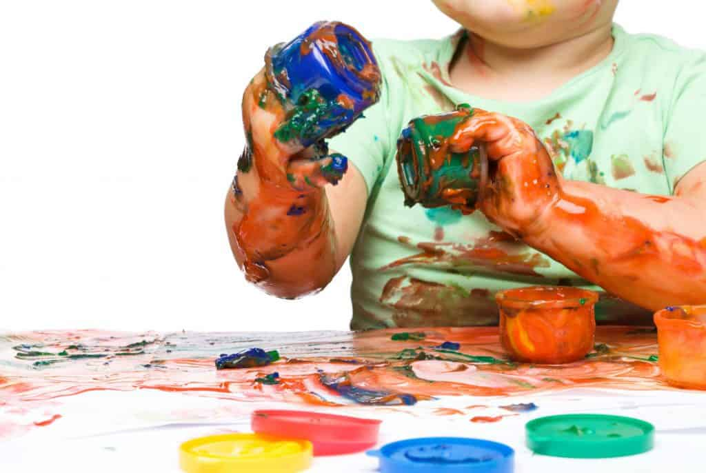 Tactile Sensory Issues for an Under-Responsive system shown by a child with paint all over their arms, hands, and shirt.