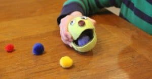 "Boy squeezing a tennis ball with a cut ""mouth"" in order for it to eat pom poms to strengthen his hands"
