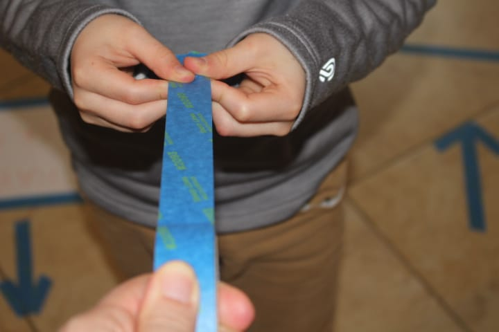Pull Painters Tape with your thumb, and pointer finger