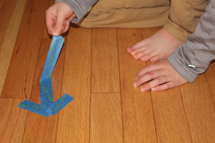 Peel Painter's Tape off of floor using thumb and pointer finger