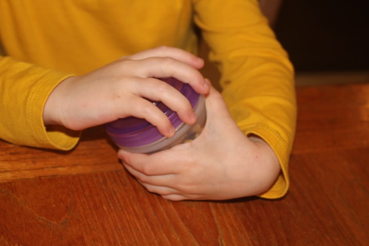 child opening a container with a screw top lid