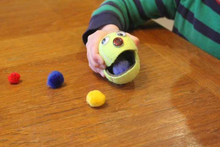 "Child squeezing tennis ball with a cut in it to open its ""mouth"" to pick up small objects"