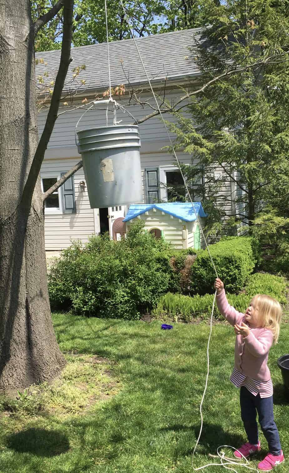 Girl using a pulley to raise a bucket by pulling a rope that is around a branch of a tree showing an example of an outdoor activity for kids that strengthens hands.