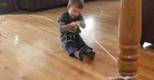 Boy sitting on the ground and pulling himself with his two hands on a rope showing an activity that can prepare them for cutting