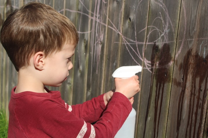 Boy using a squirt bottle to erase chalk on a fence showing an outdoor activity for kids that strengthens hands!