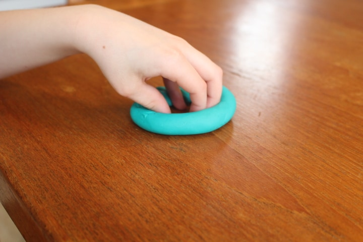 Make a ring using play dough on a table and put all your fingers inside of the ring.