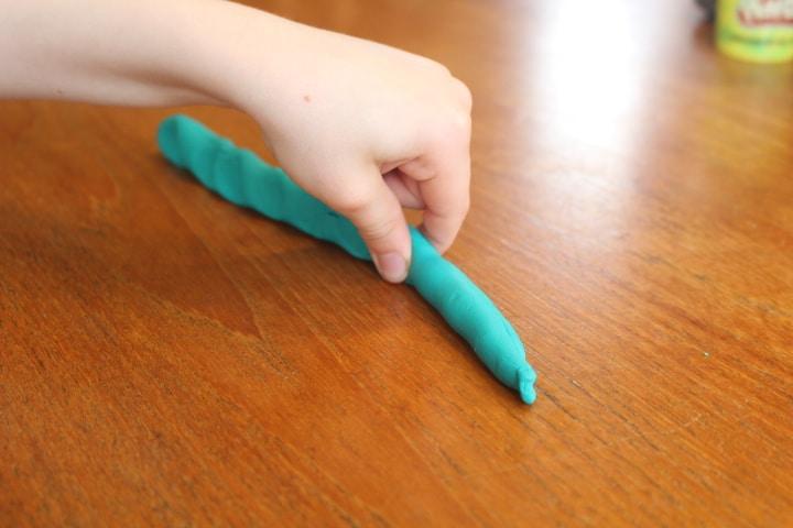 Pinching Play Dough roll