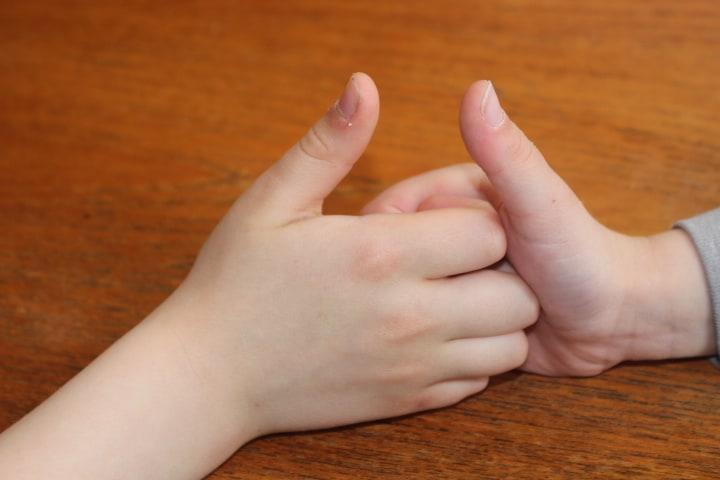 Two kids playing thumb of war