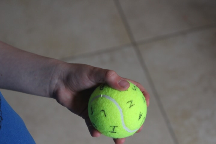 Boy holding a tennis ball in his hand with letters on it