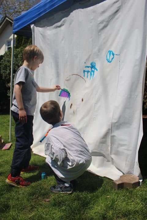 Two boys painting on a shower curtain hung up outside to show an outdoor activity for hand strengthening.