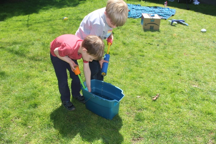 Two Boys fIlling up Foam Water Blasters with water from a bucket showing an outdoor activity for kids that strengthens hands.