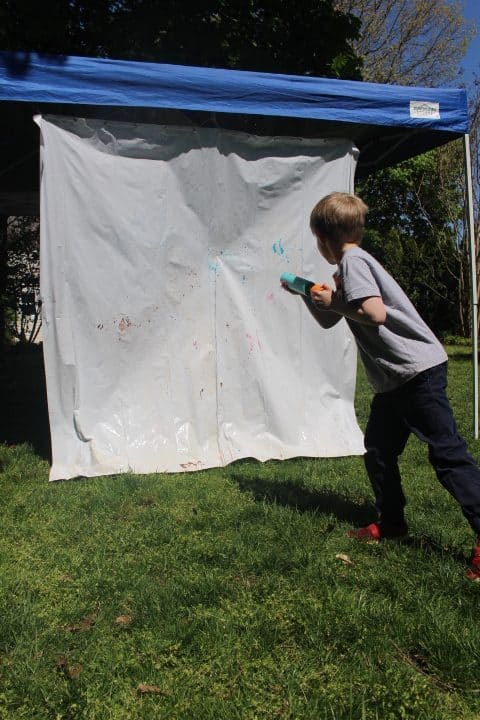 Using Foam Water Blaster, Boy is squirting water at paint on a shower curtain to strengthen his hands while playing outside.