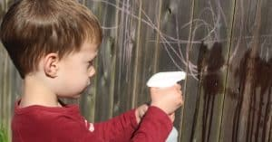Boy strengthening his hands by squirting a water bottle to erase chalk drawings on a fence