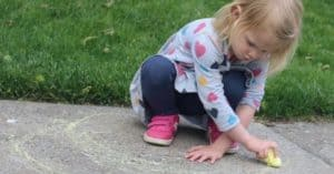 Girl squatting down and drawing a rainbow with a piece of chalk by moving her arm from one hip to the other hip crossing her midline