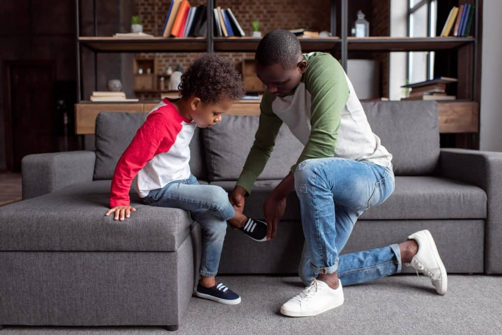 Father putting on son's shoes who has trouble crossing midline.
