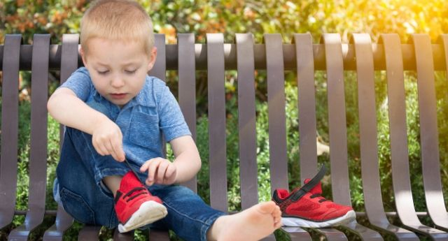 3 year old boy is sitting on a bench putting on his red shoes demonstrating a Preschool Skill.