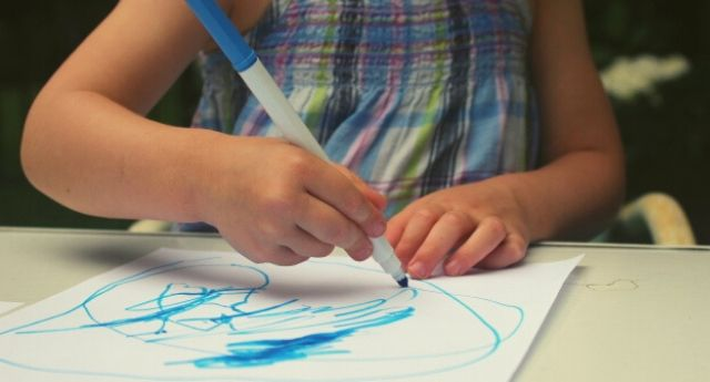 3 year old girl coloring on a paper using an emerging static tripod grasp, holding her arm in the arm rather than resting it on the table.