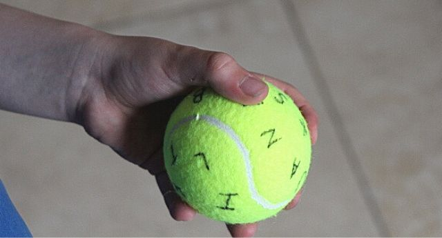 Child holding a tennis ball, in one hand, that has the alphabet randomly written on it demonstrating an in-hand manipulation skill of rotation.
