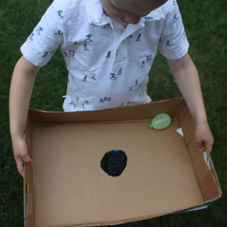 Boy holding a box lid with a whole in the middle trying to get a water balloon to drop through the hole.