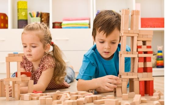 Two children buildling with blocks working on their fine motor precision.