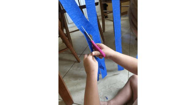 Preschooler cutting party streamer taped to a table for a preschool cutting activity