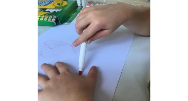 Child holding a marker between their palm and fingers while tracing their hand showing a digital pronate grasp which is part of pencil grasp development.