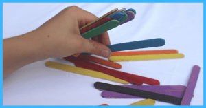 Child's hand picking up popsicle sticks with one hand demonstrating an in-hand manipulation task