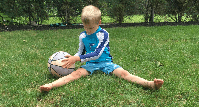 Boy wide leg sitting on the grass while holding a ball with both hands to the side.