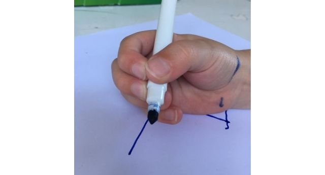 Child holding a marker with demonstrating the pencil grasp developmental stage quadrupod grasp.