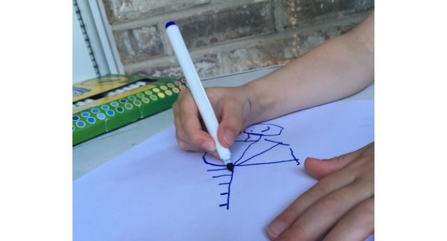 Child's hand drawing a picture with a marker demonstrating  a static tripod grasp which is one of the pencil grasp development stages.