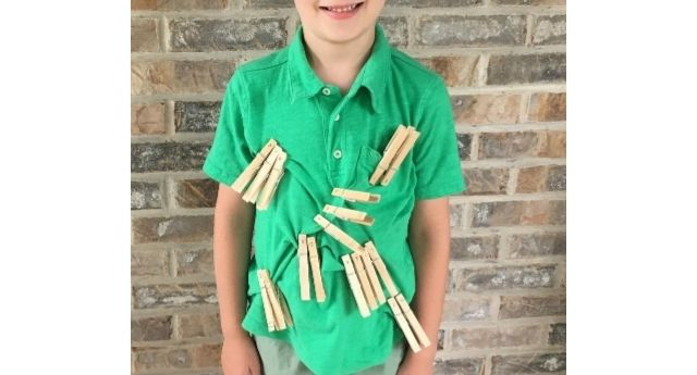Boy with groupings of clothespins spelling words out on his shirt showing a fun sight word activity!
