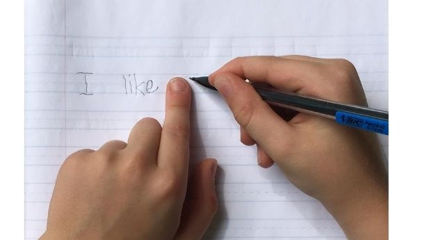 "Child holding their finger next to the word ""like"" with their pencil just to the right of their finger showing how to use your finger as a visual guide for spacing between words."