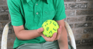 A boy holding a tennis ball with the alphabet written randomly all over it showing a fun sight word activity