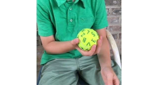 A boy holding a tennis ball with the alphabet written all over it, in one hand.