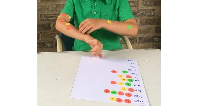 Boy peeling letter stickers off his arm crossing midline while spelling out kindergarten sight words
