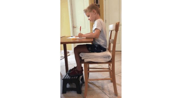 Boy writing at the kitchen table, sitting on a chair with his feet resting on a stool showing good stability in a 90-90-90 seating position.