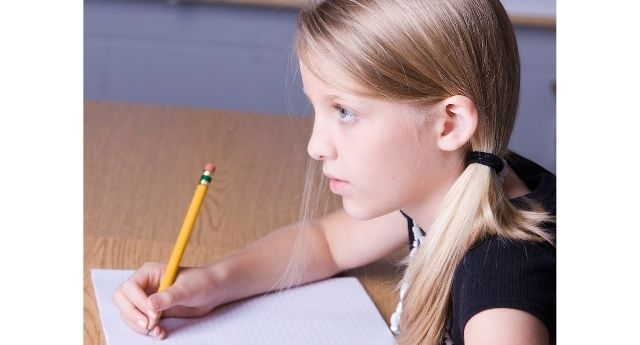 Girl staring off when she should be focusing on a writing assignment.