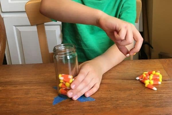 Child demonstrating a Fall themed crossing midline activity of holding a jar with one hand and picking up a piece of candy corn from a pile located on a table on the outside of his arm.