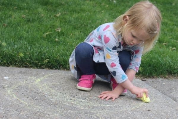 Girl showing a summer themed crossing midline activity of squatting down and drawing a rainbow with chalk.