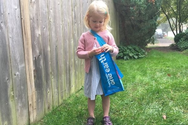 Girl using a re-useable shopping bag slung over her shoulder and across her body during an Easter Egg hunt for a crossing the midline activity.