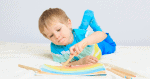 Boy laying on his stomach demonstrating a crossing midline activity with one arm bent and crosses his body while painting with a paint brush