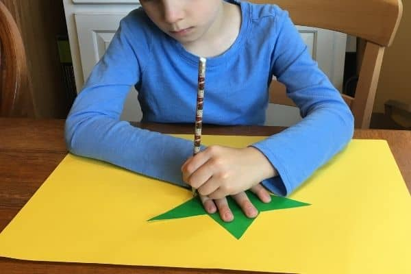 Boy demonstrating a winter themed crossing midline activity of tracing a star using a stencil.
