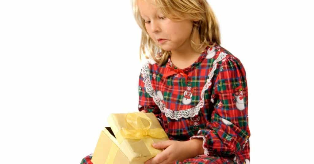 Girl anxious to open a gift demonstrating a common sensory overload in children task