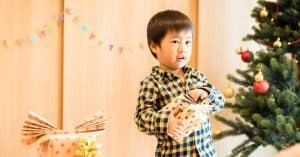 Boy opening a present but looking for reassurance that it is ok showing increased anxiety