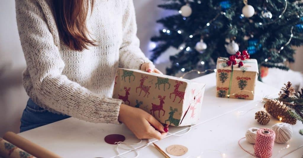 High school student wrapping Christmas gifts to help reduce Mom's sensory overload during the holidays