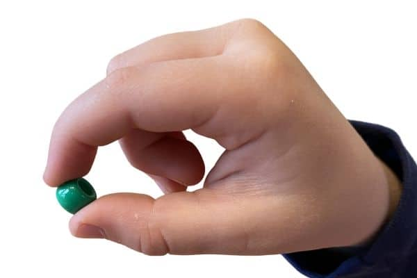 A crude, or inferior pincer grasp, demonstrated by a child holding a small bead with the pads of their pointer and thumb.