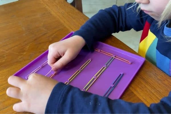 Preschooler using her thumb and pointer finger to expand a rubber band to the next peg  on a Geo Board