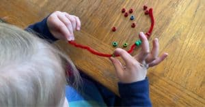 Girl stringing beads onto a pipe cleaner using a pincer grasp