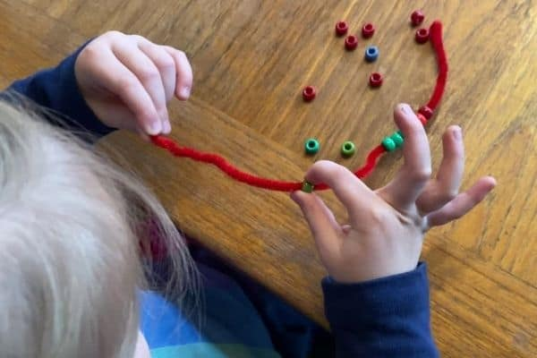 Girl stringing beads onto a pipe cleaner using a combination of a crude and neat pincer grasp.